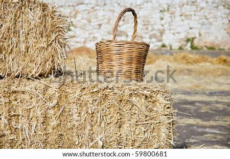 Wicker basket leaning on haistacks bales. - stock photo