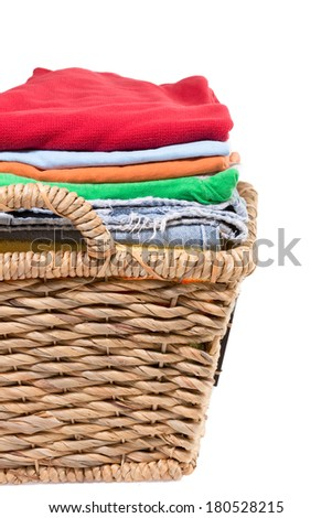 Wicker basket of clean fresh laundry filled with neatly folded clean washed clothes awaiting ironing, close up side view isolated on white - stock photo