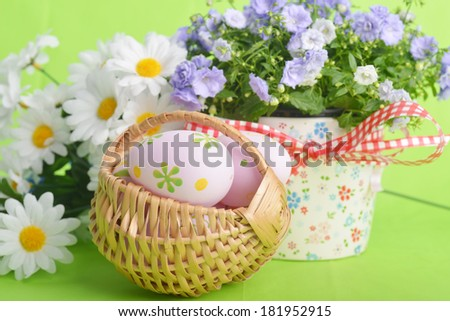 wicker basket of easter eggs with wildflowers on green background