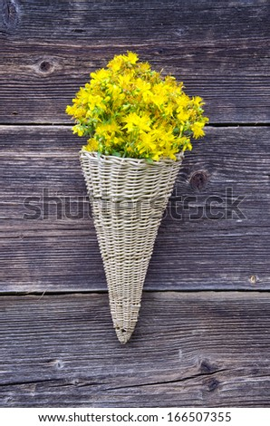 wicker basket on old farm house wall with St Johns wort medical flowers - stock photo