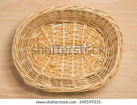 Wicker basket on wooden background - stock photo
