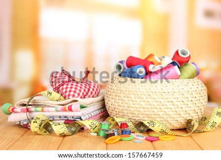 Wicker basket with accessories for needlework on wooden table, on bright background - stock photo