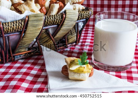 Wicker basket with artisan mini hot dogs (Sausage in the dough) with sausage on a napkin covered in mustard, mayonnaise and a glass of fresh cow's milk of the village, on a plaid background - stock photo