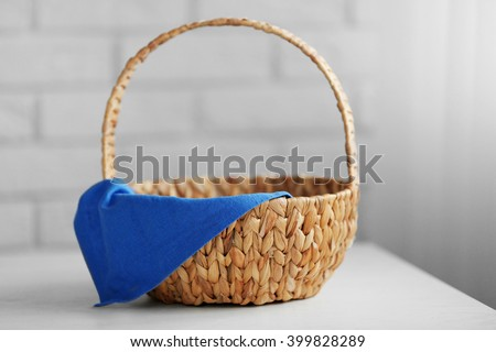 Wicker basket with blue napkin on wooden table, closeup - stock photo