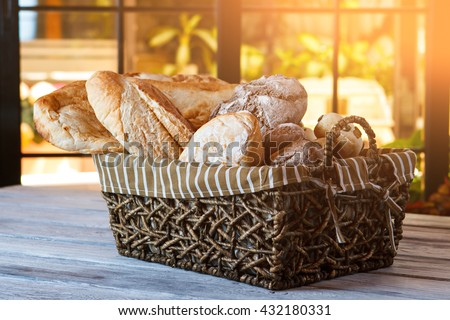 Wicker basket with bread. Bread and buns inside basket. Fresh bakery products on table. Tastes best when warm. - stock photo
