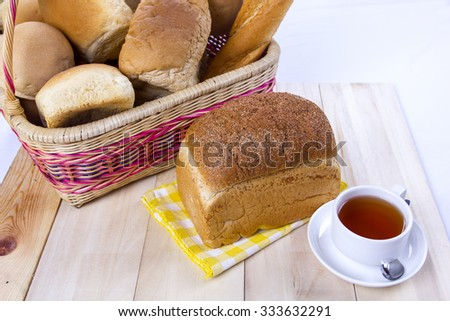 Wicker basket with brown bread and tea on a white background - stock photo