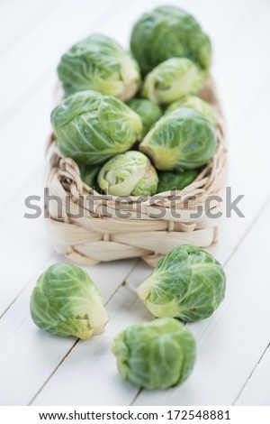 Wicker basket with brussels sprouts, white wooden background - stock photo
