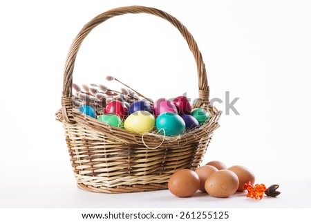 Wicker basket with colored eggs and willow branches on a white background. Happy Easter. - stock photo