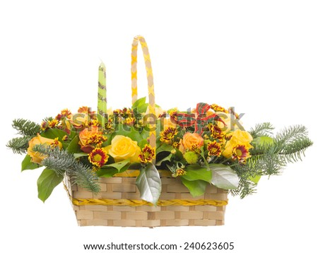 wicker basket with colorful flowers, fir branches covered with silver, a green candle and a red bow - stock photo