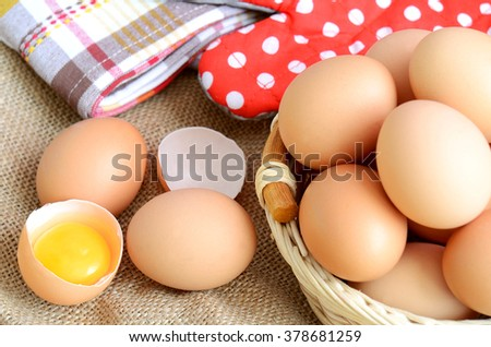 Wicker basket with eggs and broken raw egg with the yolk and albumen on a linen tablecloth with a striped dish towel and red potholder with white polka dots