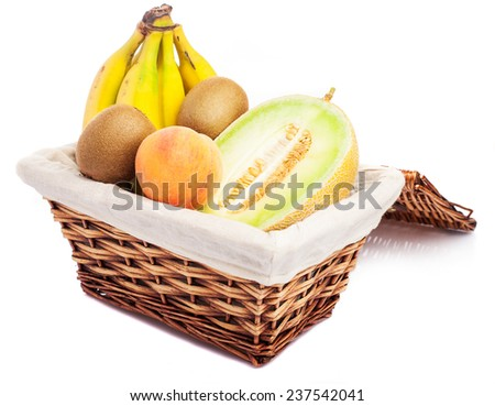 wicker basket with fruit inside on a white background - stock photo