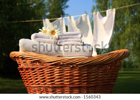wicker basket with laundry against a blue sky- late afternoon - stock photo