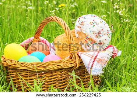 Wicker basket with painted eggs and Easter cake on the spring green grass, close up - stock photo