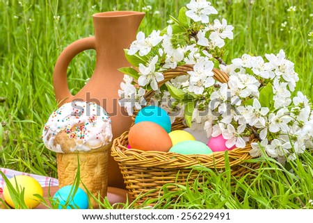 Wicker basket with painted eggs, Easter cakes, a clay jug and flowering branch cherry in the spring garden - stock photo