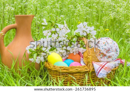 Wicker basket with painted eggs, Easter cakes, a clay jug and flowering branch cherry in the spring garden on the green grass - stock photo