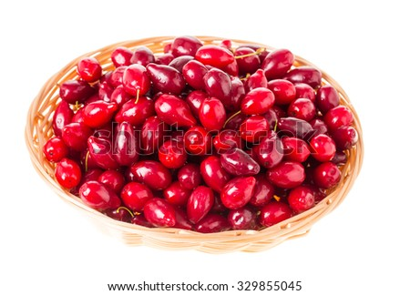 Wicker basket with red ripe dogwood berries. Isolated on a white background. - stock photo
