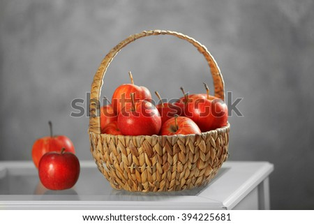 Wicker basket with ripe apples on white table - stock photo