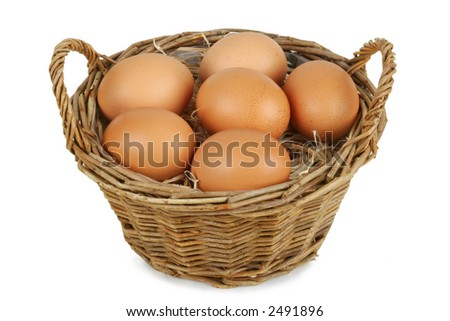 Wicker basket with six brown eggs. Isolated on white. Clipping path included. - stock photo