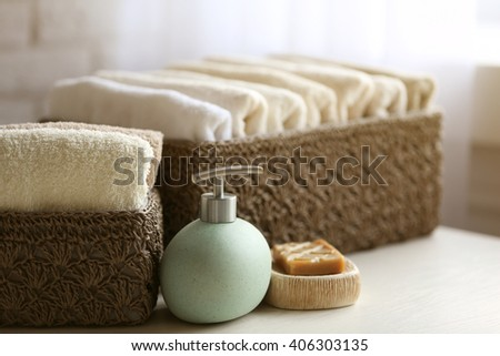 Wicker basket with towels inside and soap on wooden table background - stock photo