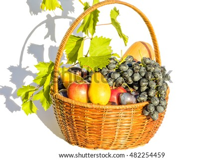 Wicker basket with various fruits and green grape leaves, isolated on a white background. Selective focus