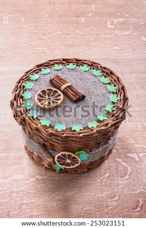 wicker basket without handle on old wooden board  - stock photo
