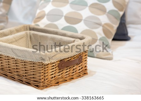 Wicker baskets in different size on a white bed. - stock photo