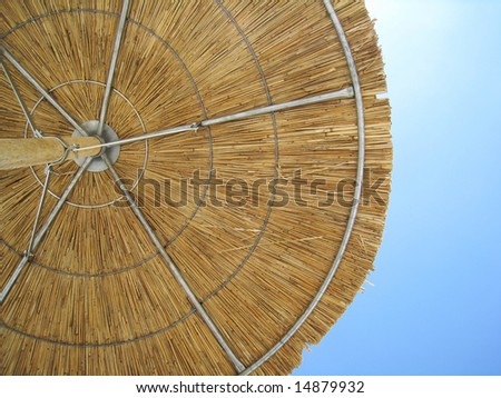 wicker beach umbrella against sky - stock photo