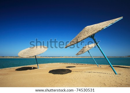 Wicker Beach Umbrella with wicker wind breaks. - stock photo