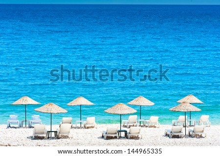 wicker beach umbrellas on the beach - stock photo