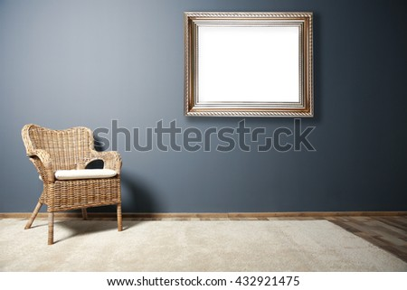 Wicker chair and picture frame on dark grey wall background - stock photo