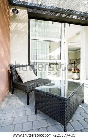 Wicker chair and table situated in garden - stock photo