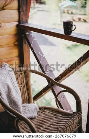 Wicker chair on a cozy balcony in a wooden house