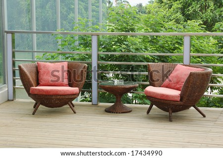 Wicker chairs on the patio in a beautiful garden. - stock photo
