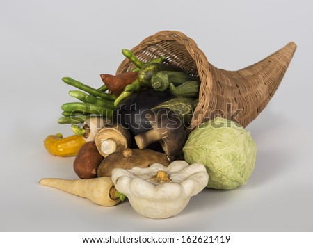 Wicker cornucopia overflowing with vegetables on gray - stock photo