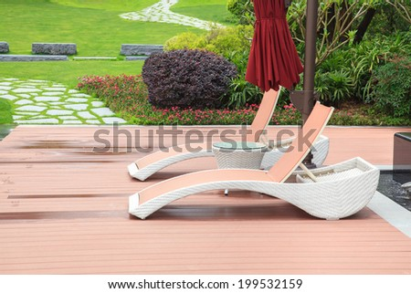Wicker deck chair and table in the beautiful summer park with green lawns and flowerbed - stock photo