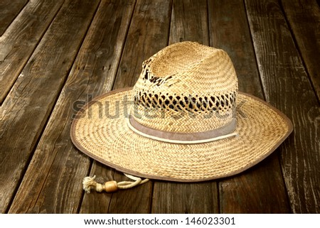 wicker hat on wooden table - stock photo