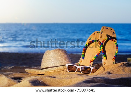 Wicker hat, sandal and glasses on the sandy beach - stock photo
