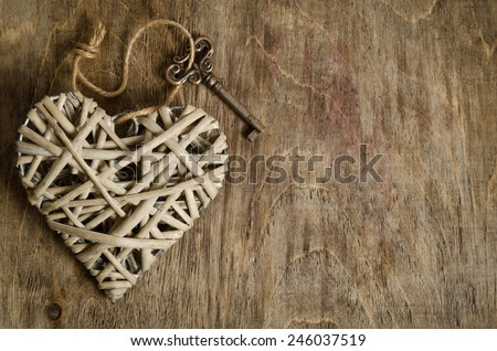 wicker heart handmade with the key lying on a wooden base . top view - stock photo