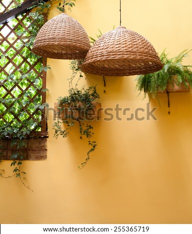 Wicker lamp shade against a background of yellow wall - stock photo
