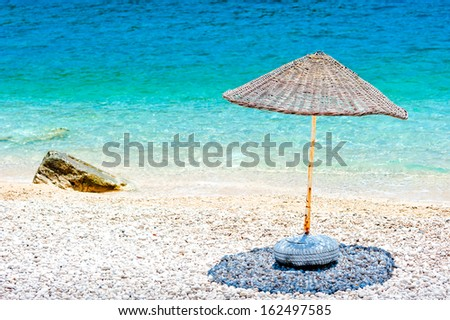 wicker parasol on the beach at the water's edge - stock photo