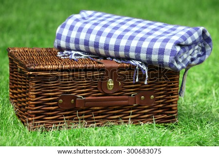 Wicker picnic basket  and plaid on green grass, outdoors  - stock photo