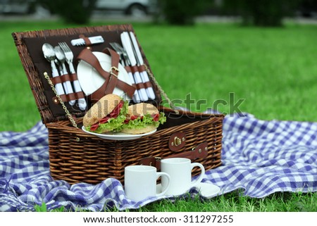 Wicker picnic basket, tasty sandwiches, tea cups  and plaid on green grass, outdoors  - stock photo