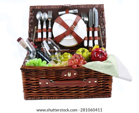 Wicker picnic basket with food, tableware and tablecloth isolated on white - stock photo