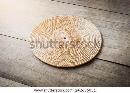 Wicker placemat on wooden table background - stock photo