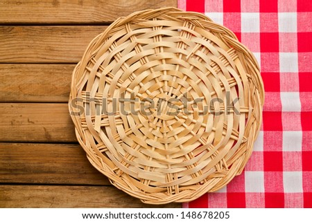 Wicker plate on checked tablecloth over wooden background - stock photo