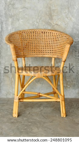 wicker/rattan chair on cement wall background  - stock photo