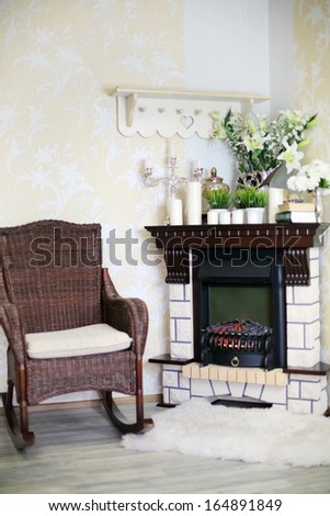Wicker rocking chair and fireplace with candles and flowers in cosy room.  - stock photo