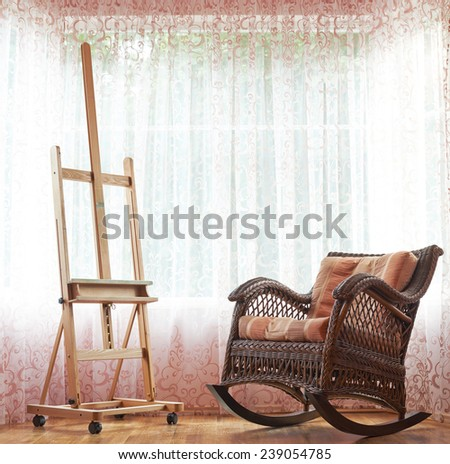 Wicker rocking chair and wooden easel composition against the window's curtains background - stock photo