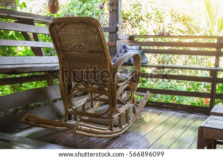 Wicker rocking chair on a wooden house in the old atmosphere in the ...