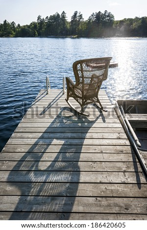 Wicker rocking chair on wooden dock in summer at small lake casting long shadow - stock photo